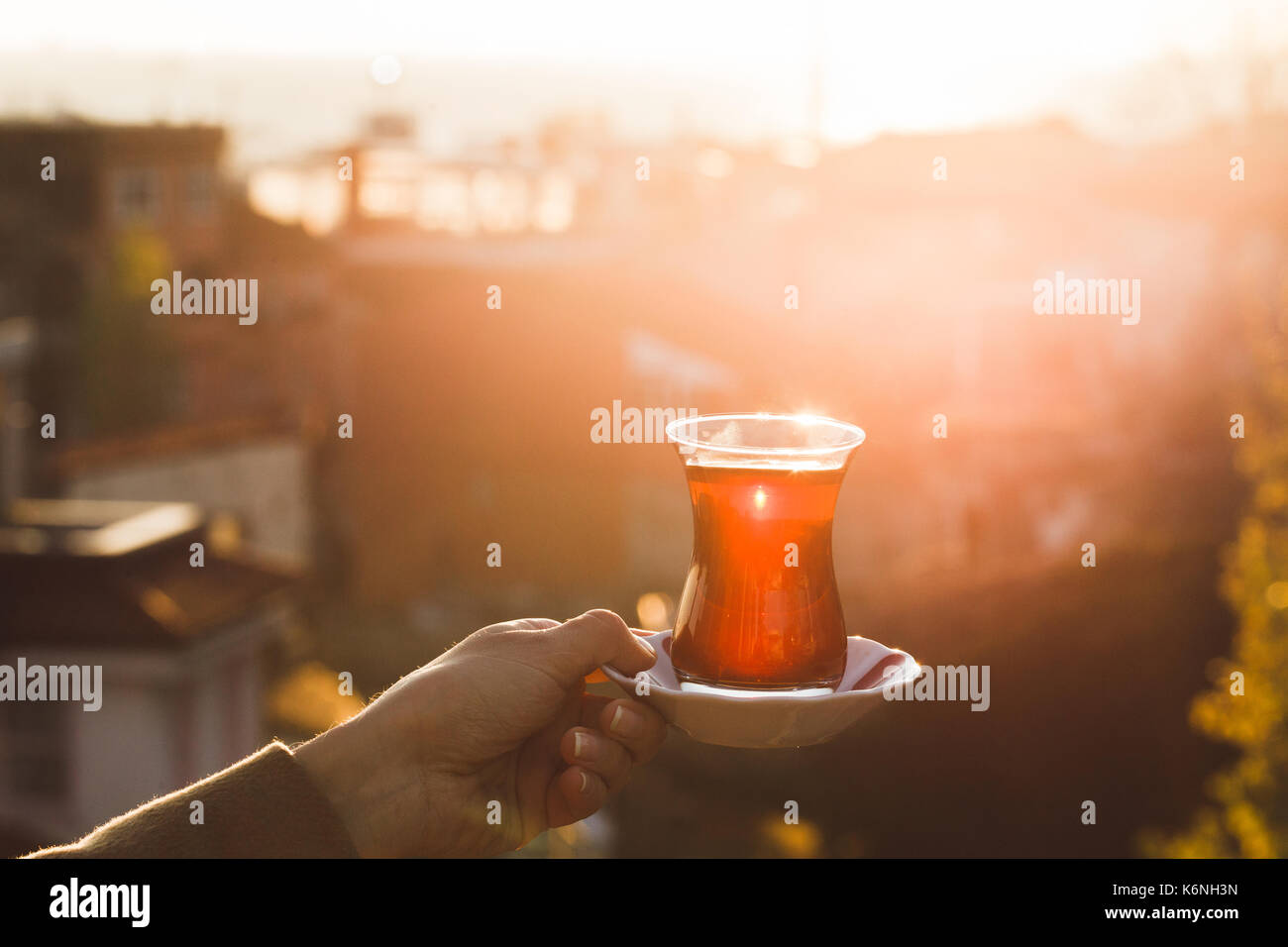 Hand holding a cup of traditional Turkish tea illuminated and transparent by the warm evening sunlight. Sunset teatime - Stock Image