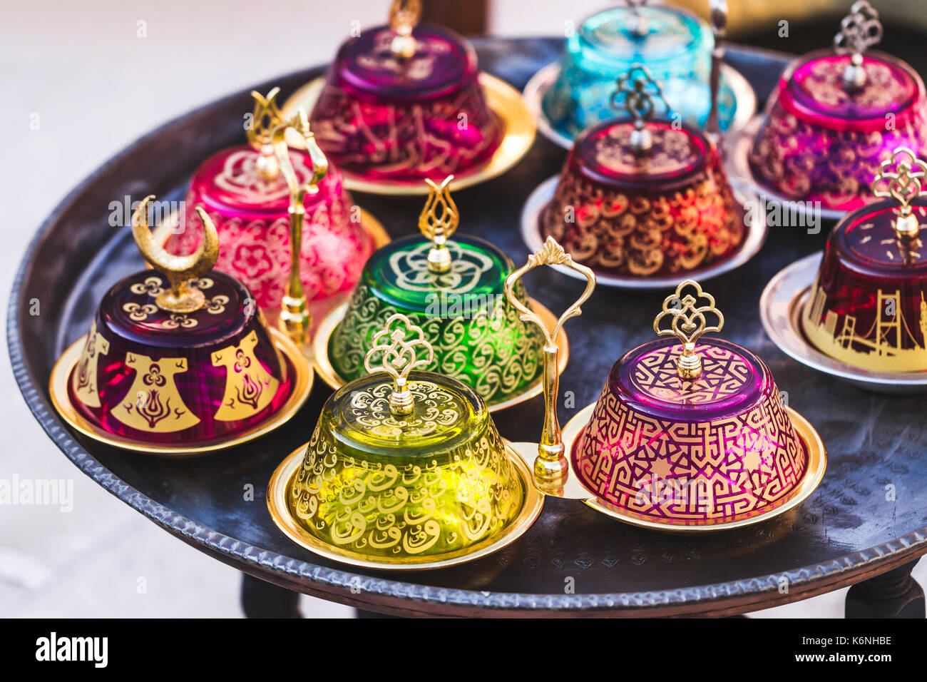 Stack of handmade multicolor Turkish dishes on the market. Vintage plates on round table - Stock Image