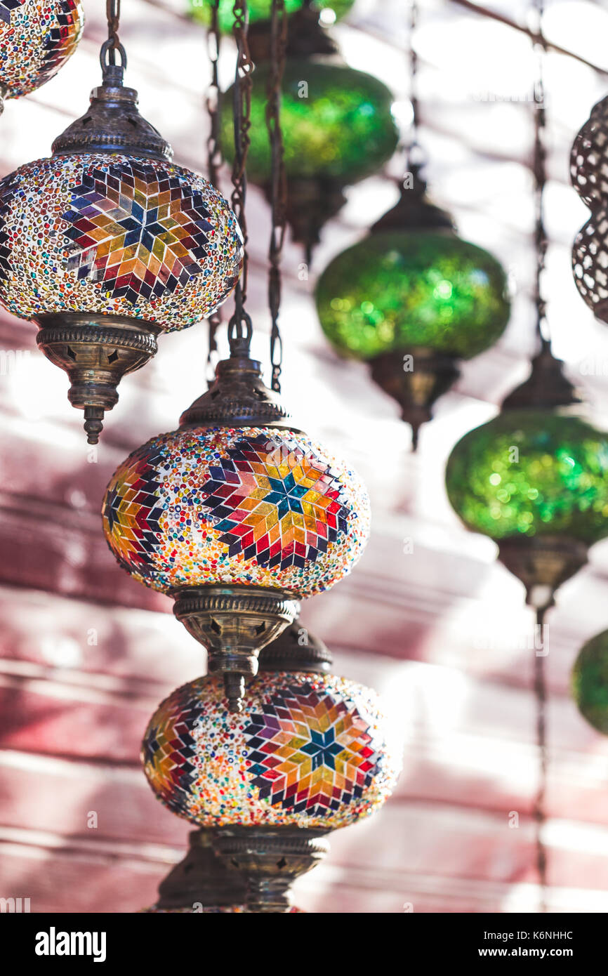 Beautiful traditional handmade turkish lamps in souvenir shop. Mosaic of colored glass close up - Stock Image