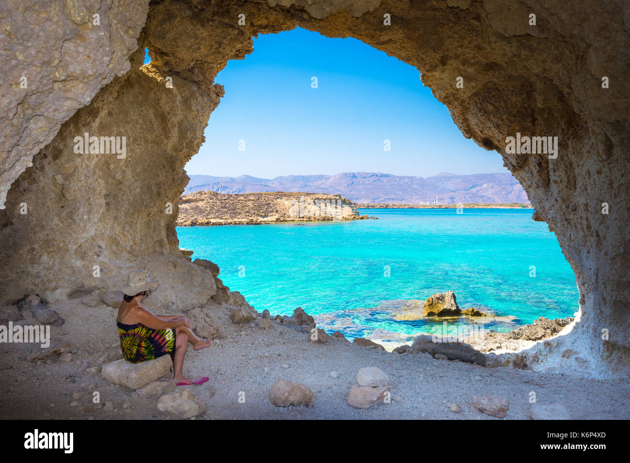 Amazing summer view of woman in a cave at Koufonisi island with magical turquoise waters, lagoons, tropical beaches - Stock Image