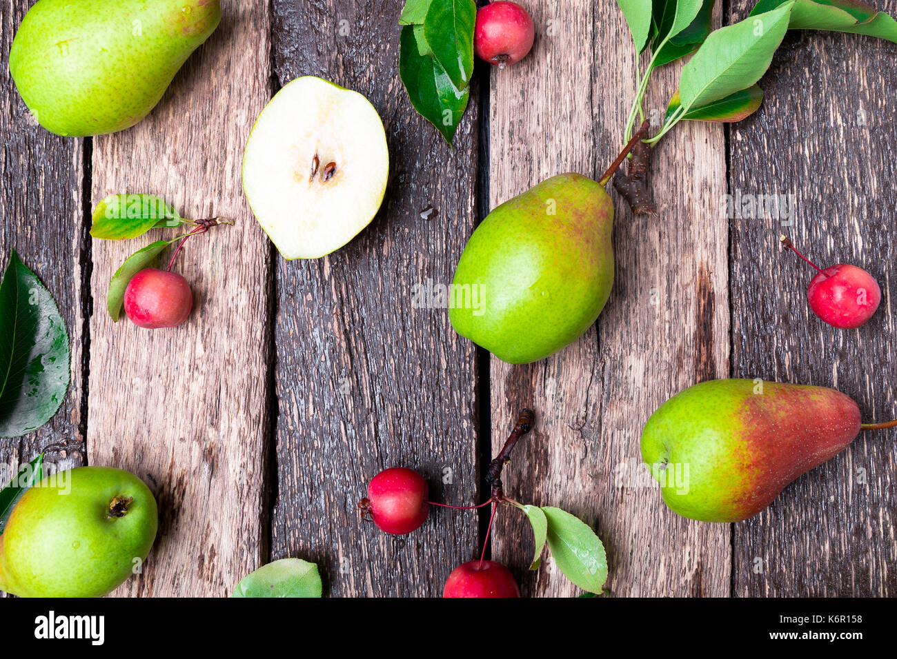 Pear and small apple on wooden rustic background. Top view. Frame. Autumn harvest - Stock Image
