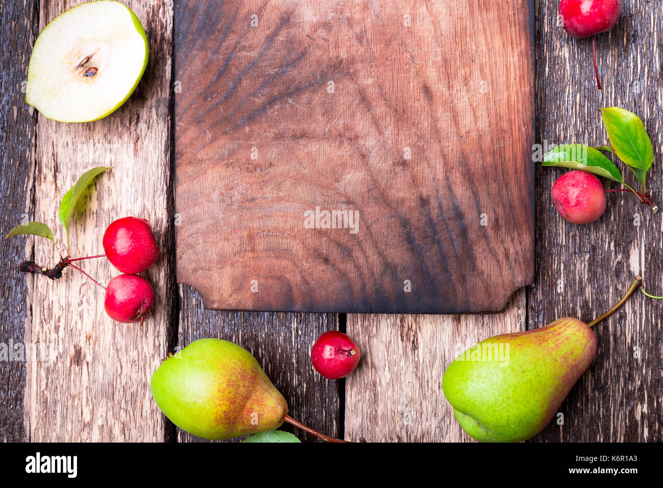 Pear and small apple around empty cutting board on wooden rustic background. Top view. Frame. Autumn harvest. Copy - Stock Image