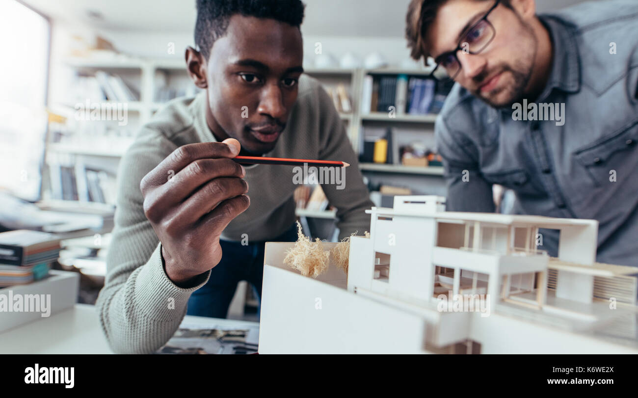 Two male architects in office discussing construction project. Young men working together on new building model. - Stock Image