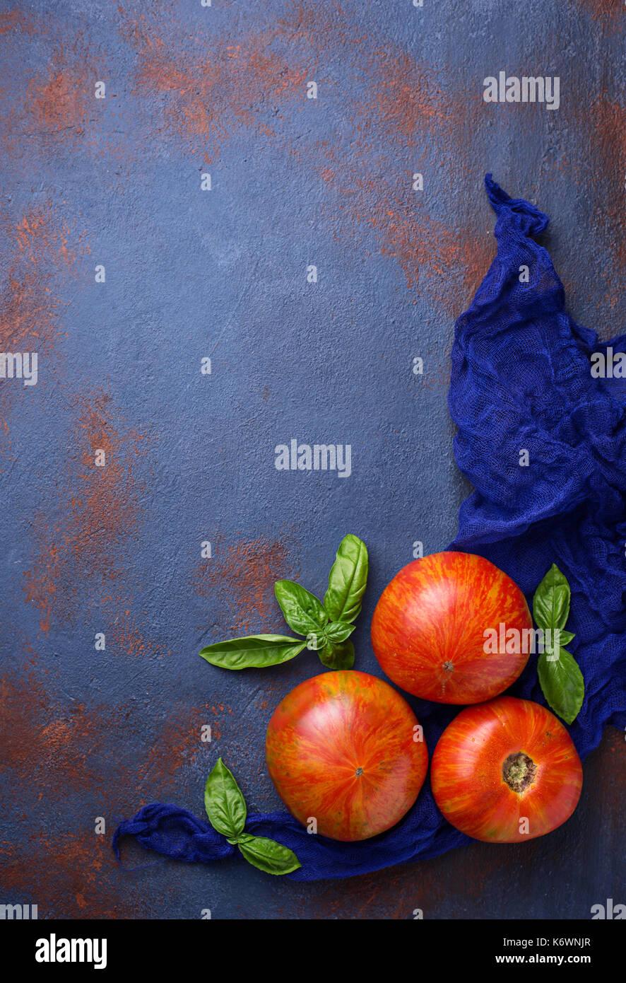 Fresh tomato on blue rusty background.  - Stock Image