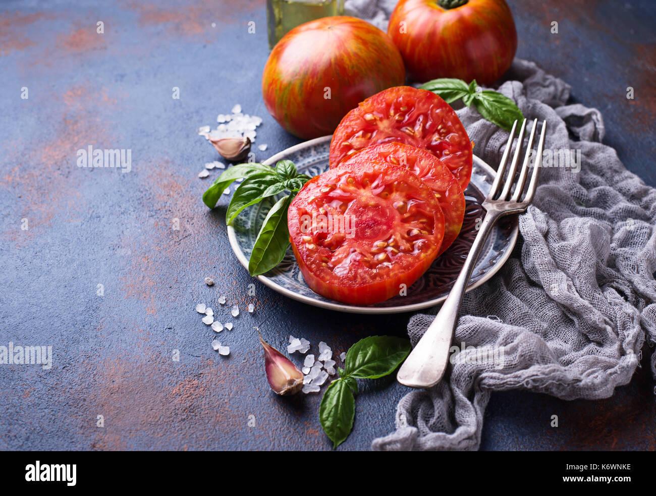 Sliced tomato on blue rusty background - Stock Image