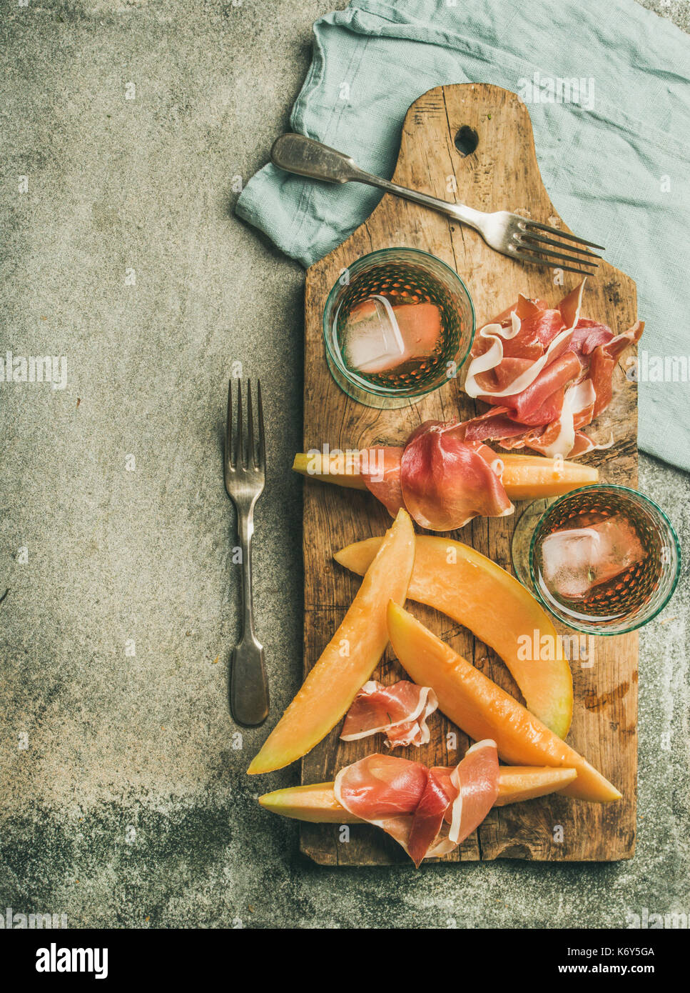 Flatlay of rose wine, prosciutto ham, melon, copy space - Stock Image