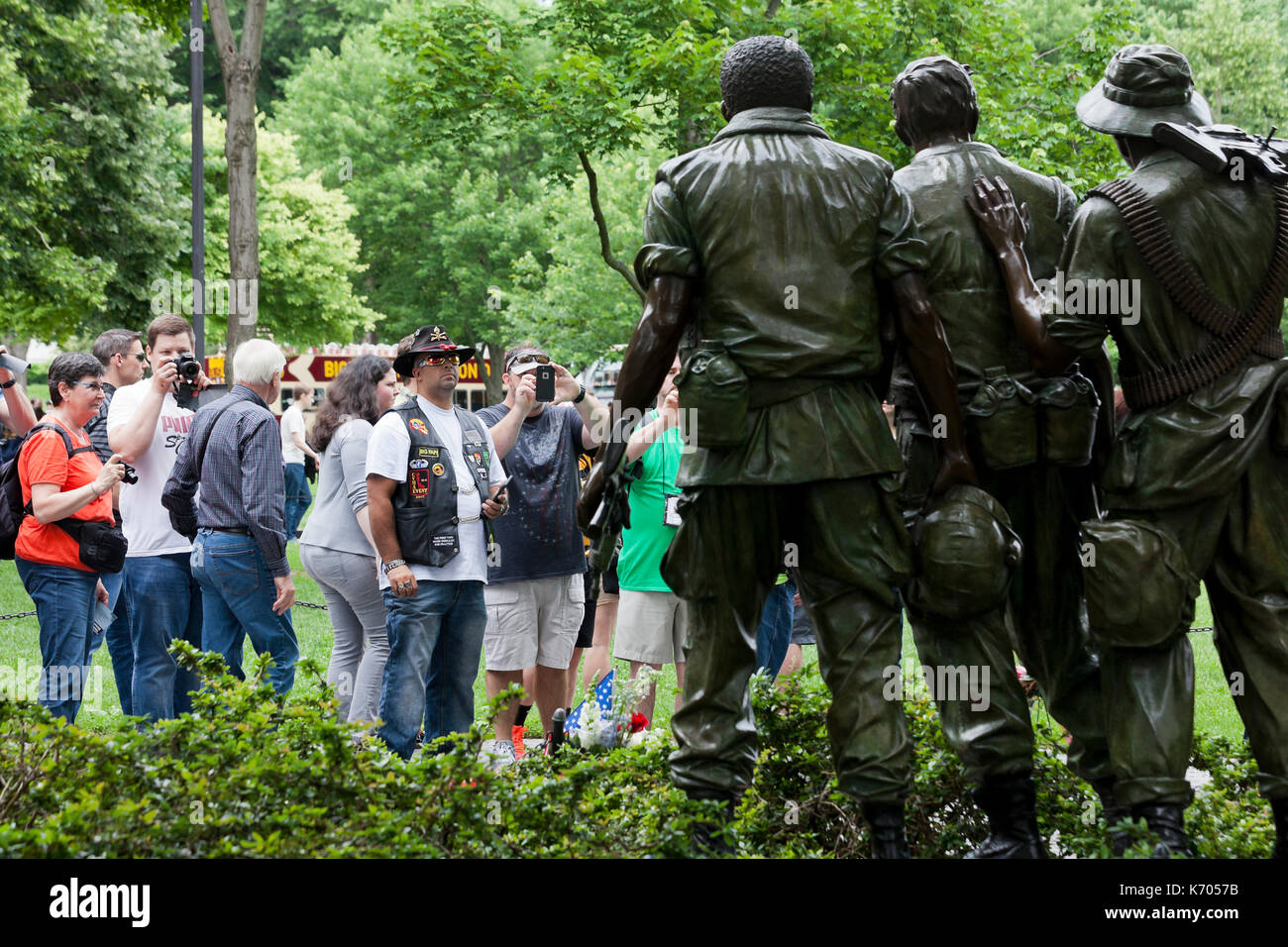 Visitors view and photograph the Three Soldiers statue at the Vietnam War  memorial - Washington,