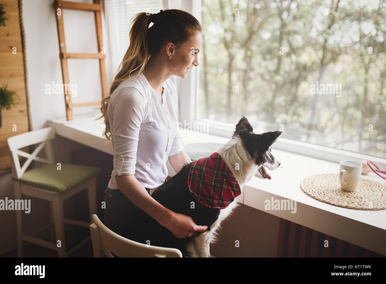 Beautiful woman happy while spending time with her dog at home - Stock Image