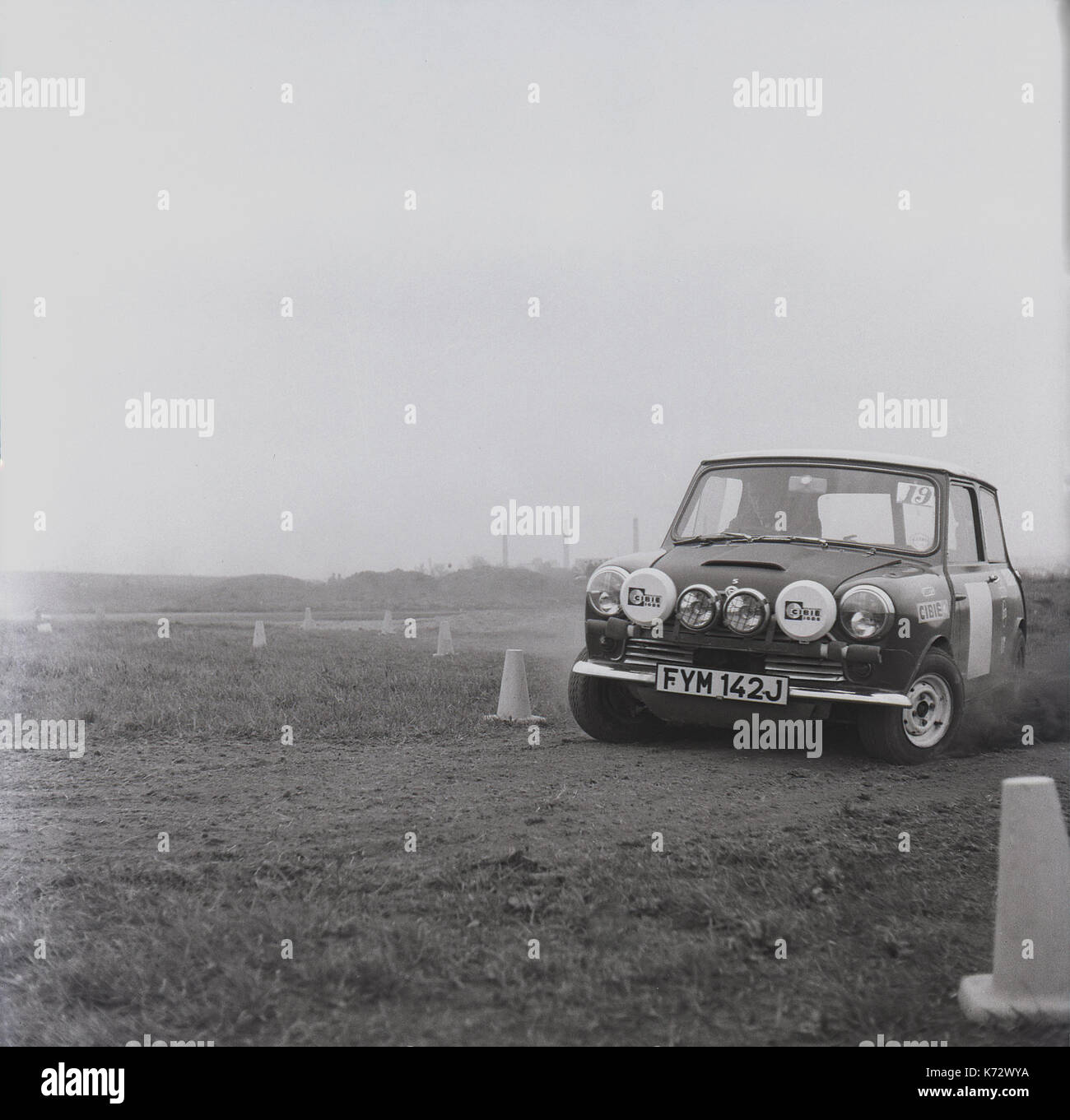1970s, historical, a specially modified works mini taking a corner at speed while racing on a gravel test track - Stock Image