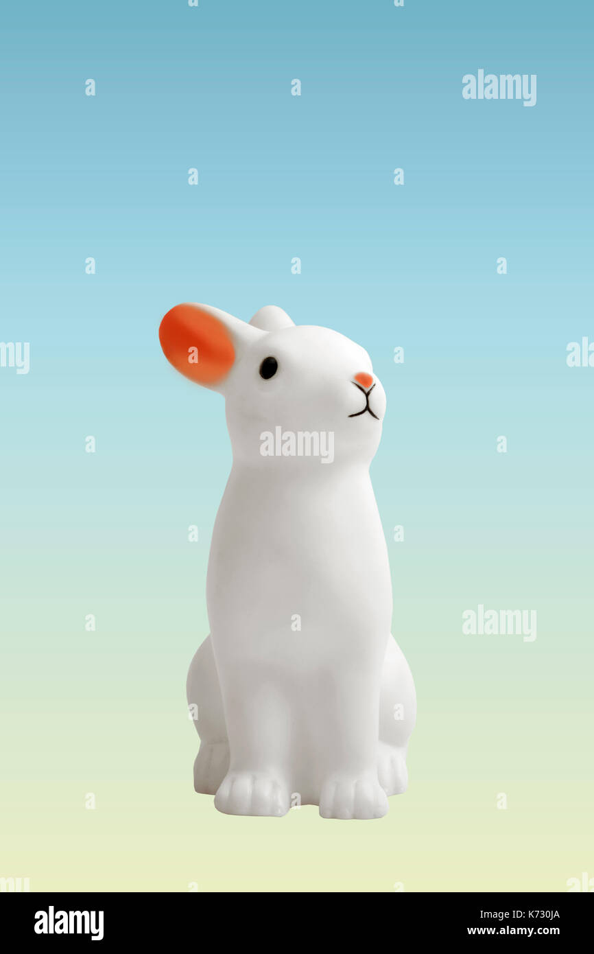a cute white plastic bunny on a pastel gradient blue and yellow background. Minimal color still life photography - Stock Image