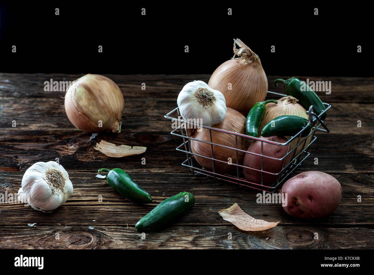 A still life photo of assorted veggies such as garlic, potatoes, peppers, and onions. - Stock Image