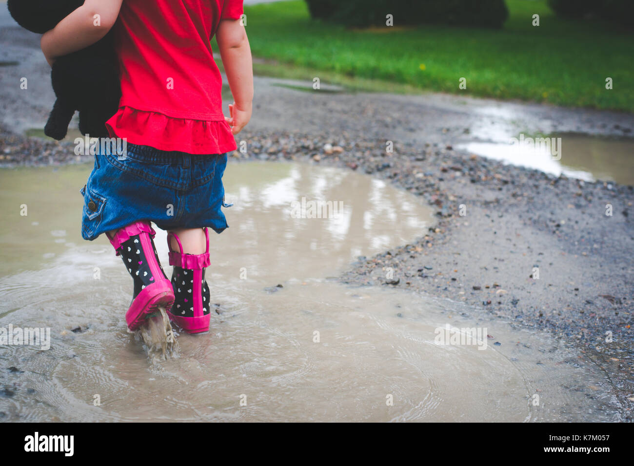 A toddler walking in a mud puddle in rain boots carrying a stuffed animal - Stock Image