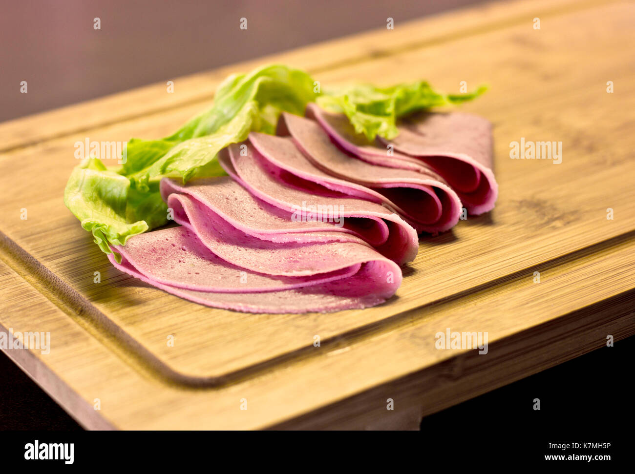 Thinly sliced sausage with green salad on wooden board - Stock Image