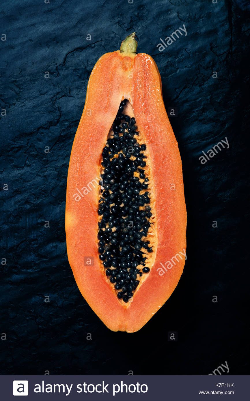 Papaya (Paw Paw) sliced in half and viewed from above on dark blue black slate rock - Stock Image