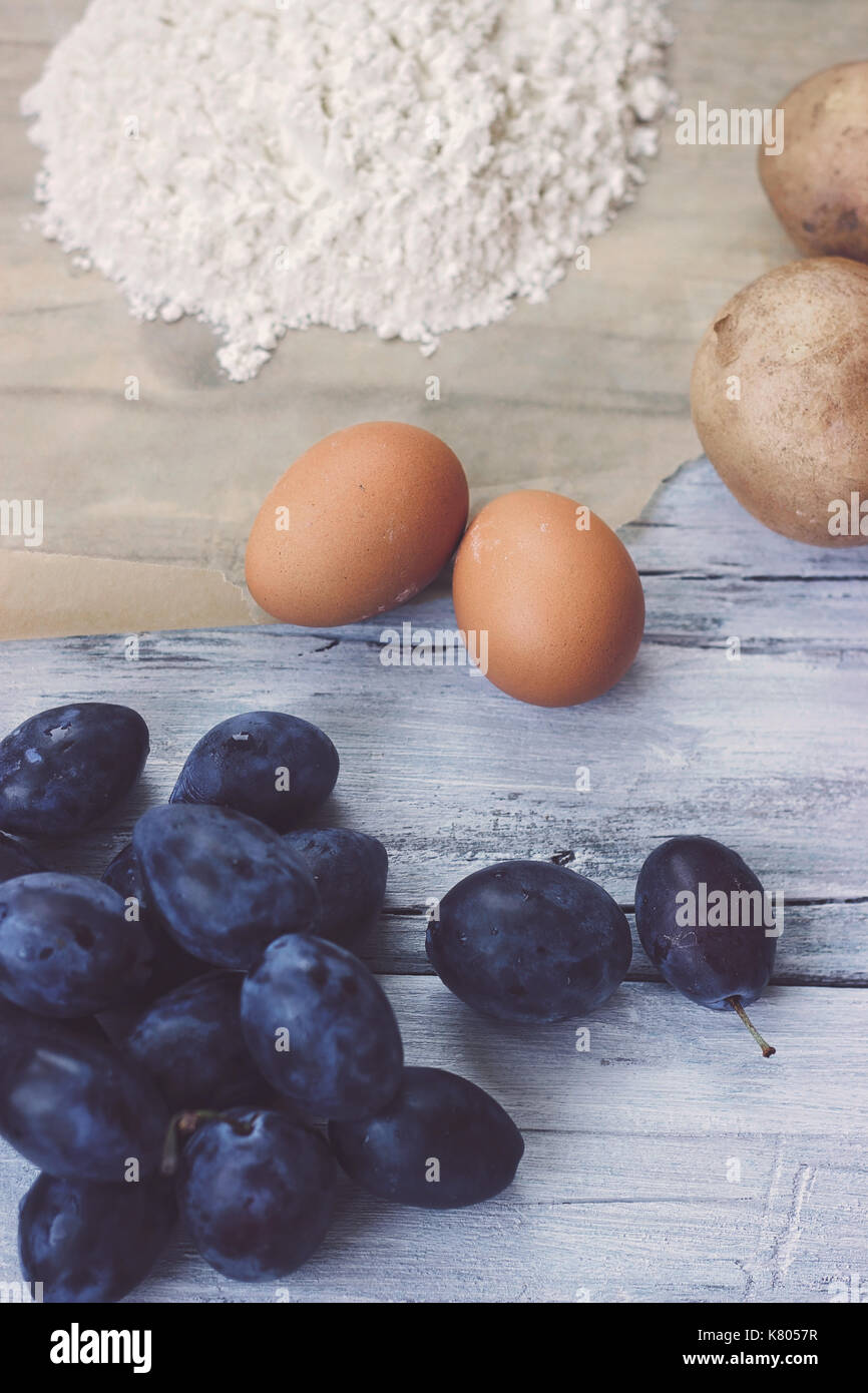Ingredients for plum dumplings - plums, flour, eggs and potatoes - Stock Image