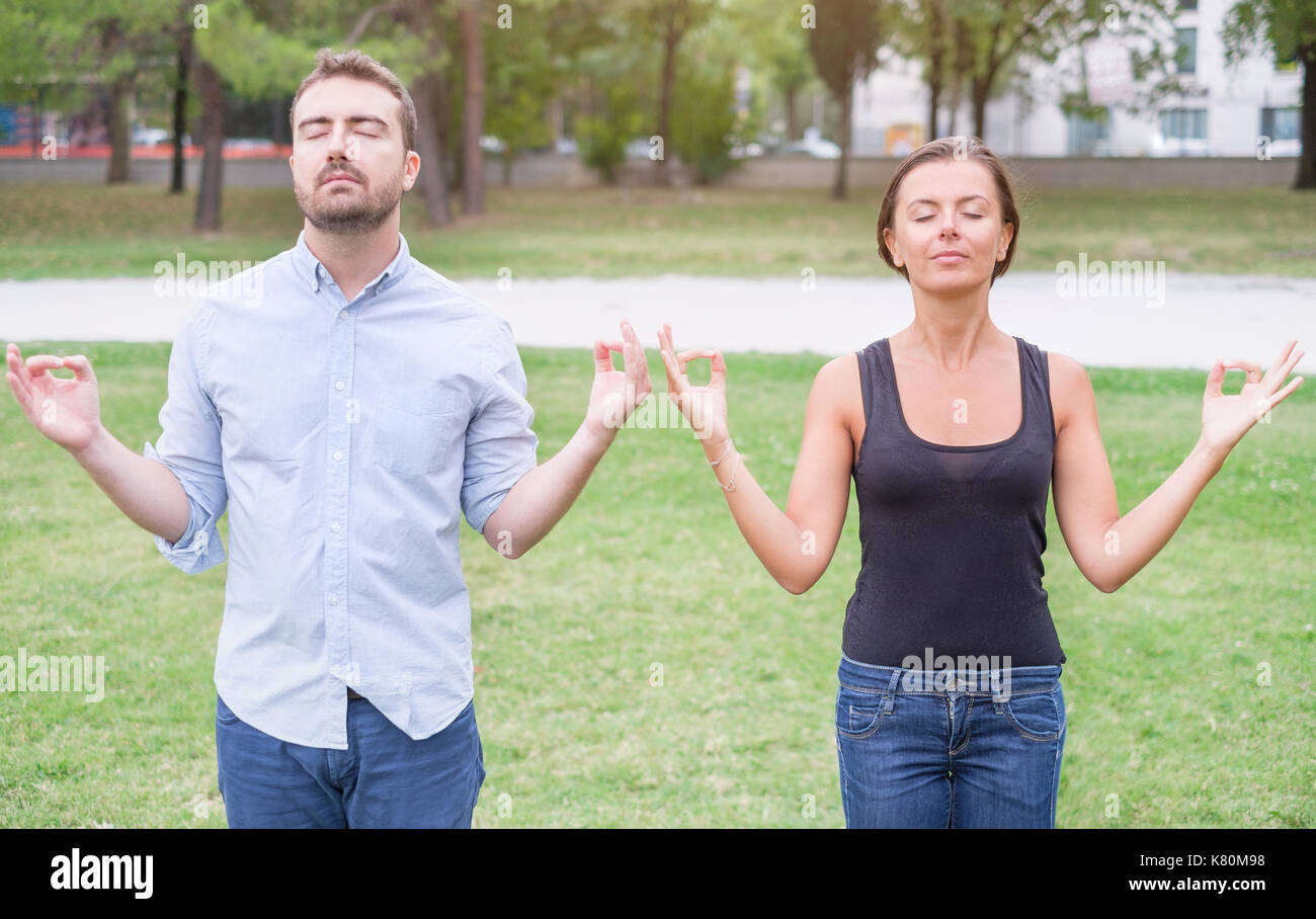 Profile of a couple of man and woman meditating together in the nature - Stock Image