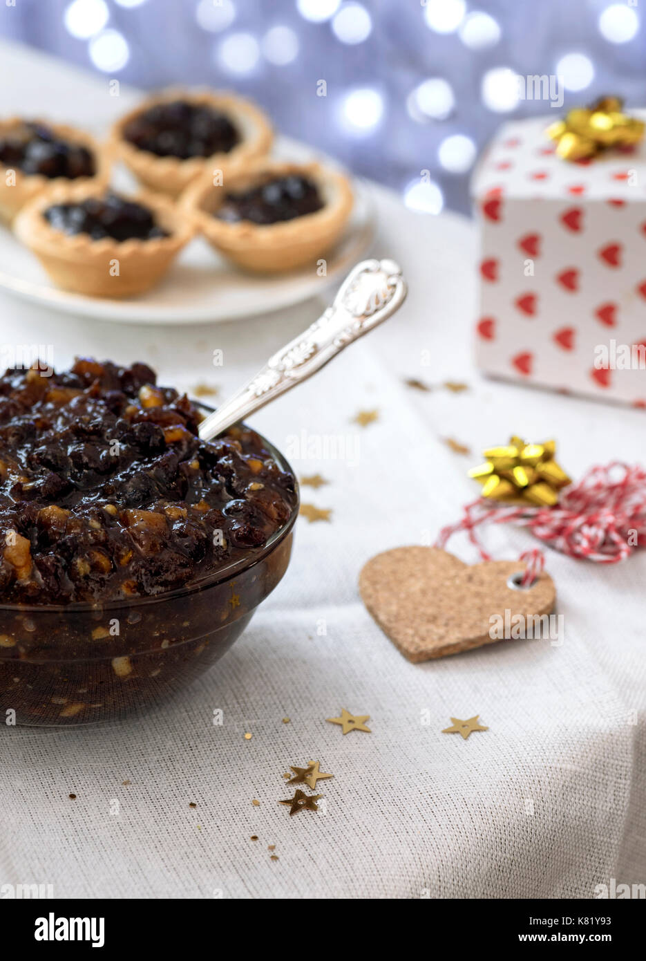 arrangement of homemade traditional Christmas mincemeat  focus on the subject,  with mince pies and bokeh lights - Stock Image