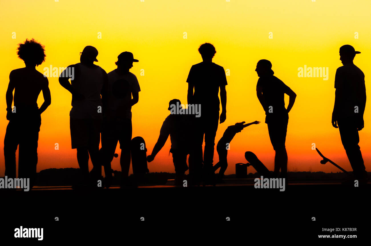silhouette-of-a-group-of-young-skateboarders-at-sunset-K87B3R.jpg