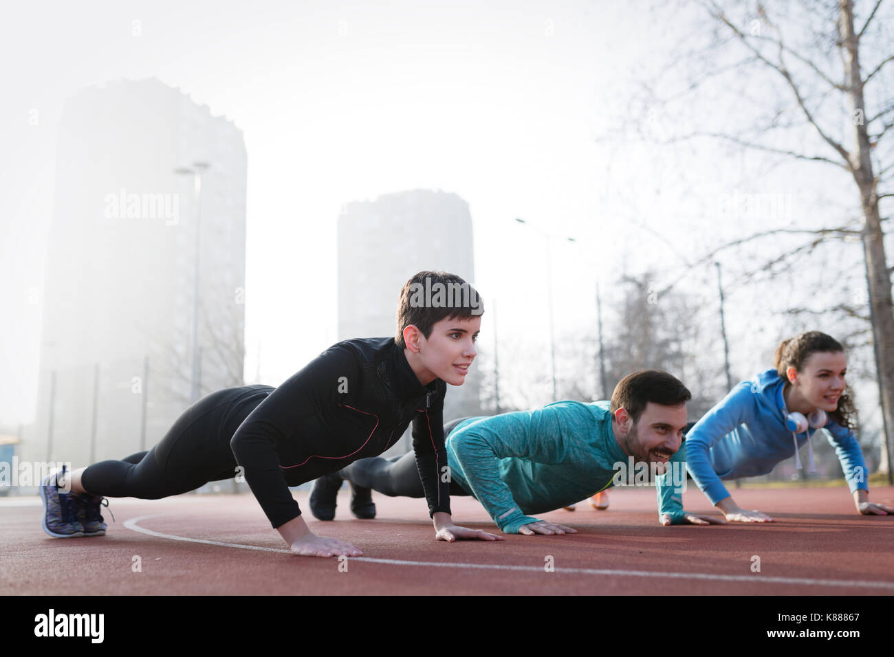 Group of healthy sporty determined friends fitness training toge - Stock Image