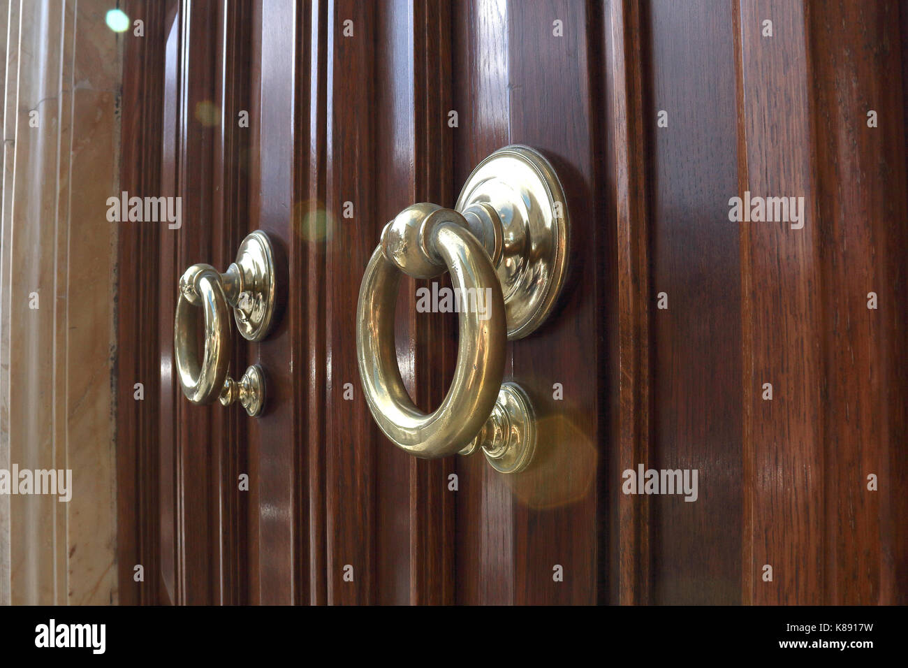 Gold ring door knockers, wooden door in marble frame. Shallow focus. Rome, Italy. - Stock Image