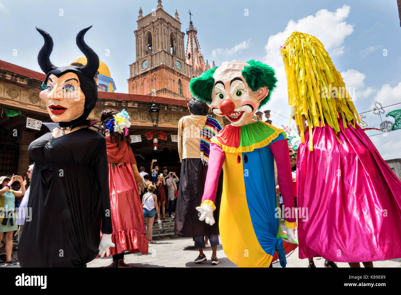 Giant papier mâché puppets called mojigangas dance in front of the Parroquia de San Miguel Arcangel church - Stock Image