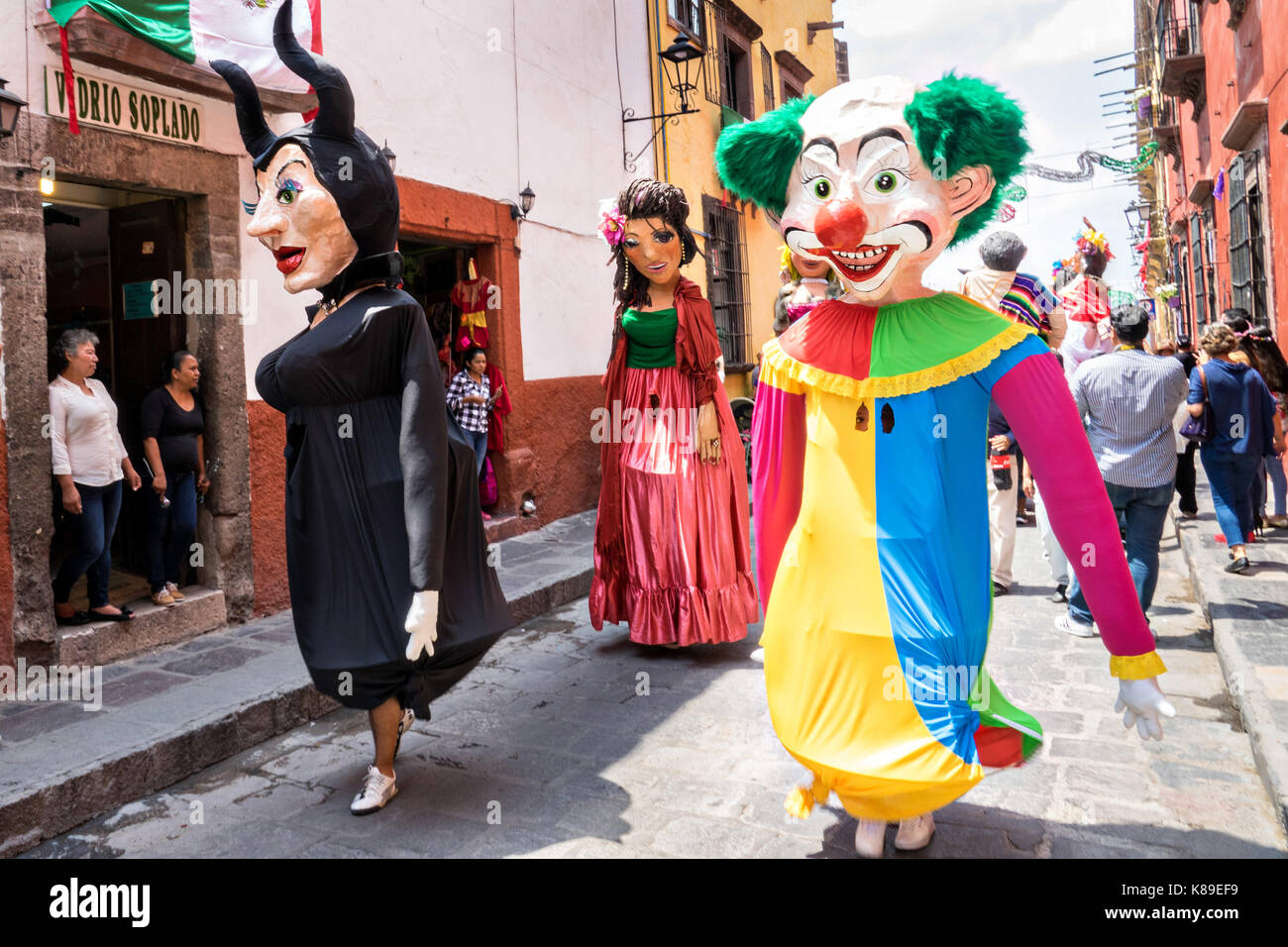 Giant papier mache puppets called mojigangas dance in the streets during a children's parade celebrating Mexican - Stock Image