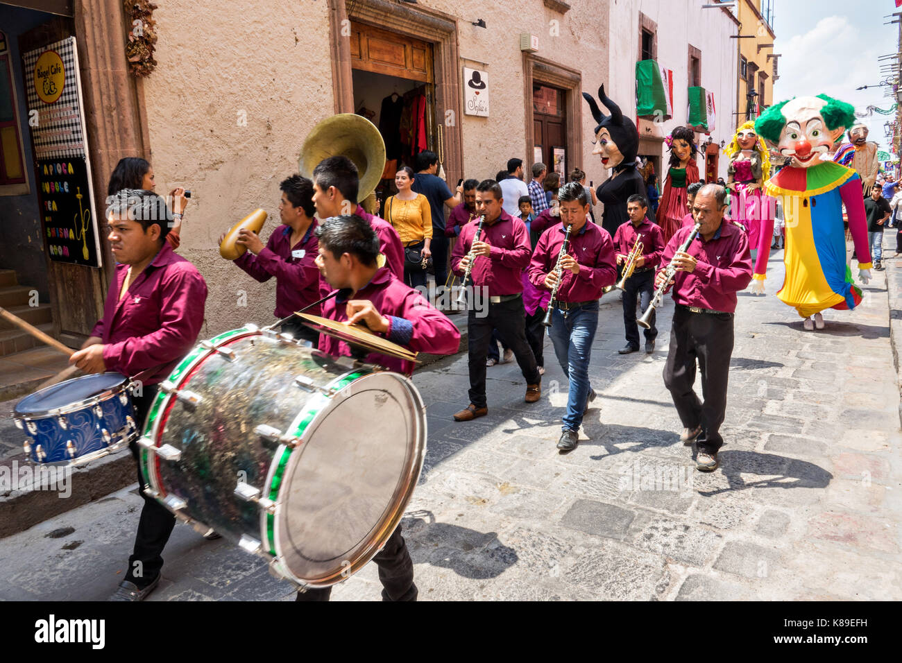 A brass band leads a procession of giant papier mache puppets called mojigangas in the Jardin Allende during a children's - Stock Image