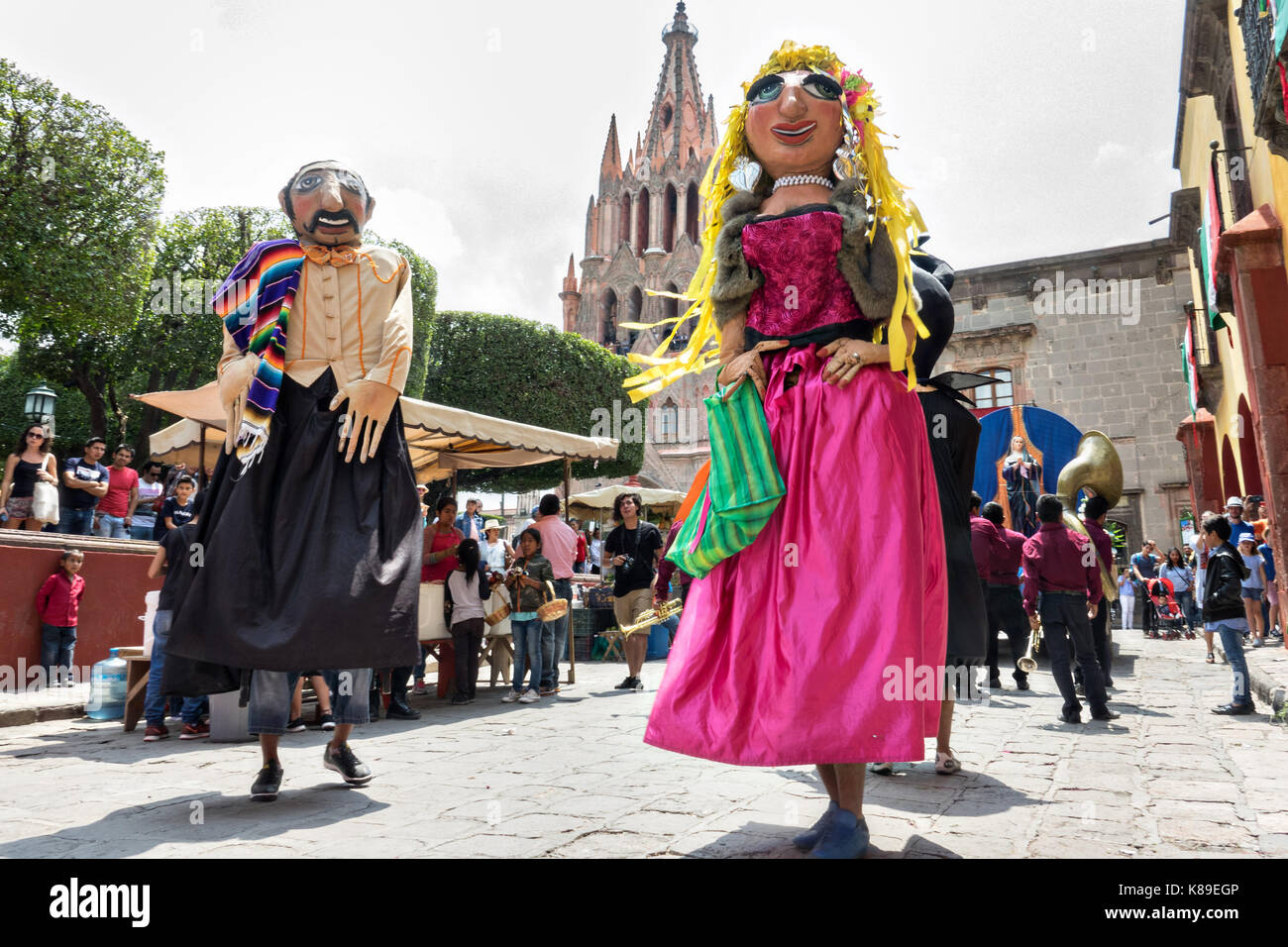 Giant papier mache puppets called mojigangas dance in front of the Parroquia de San Miguel Arcangel church during - Stock Image