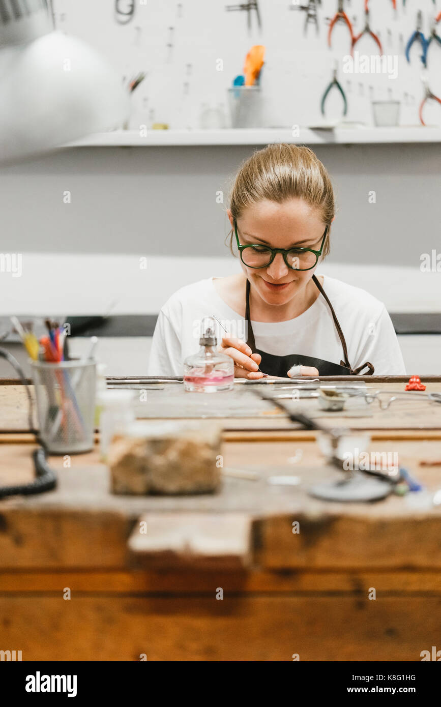 Female jeweller working with miniature hand tool at workbench - Stock Image
