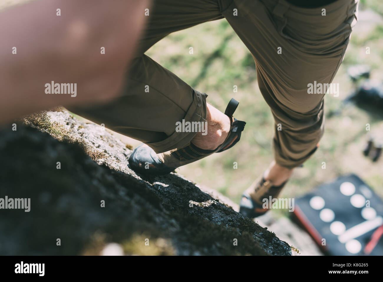 Waist down view of male boulderer climbing up boulder, Lombardy, Italy - Stock Image