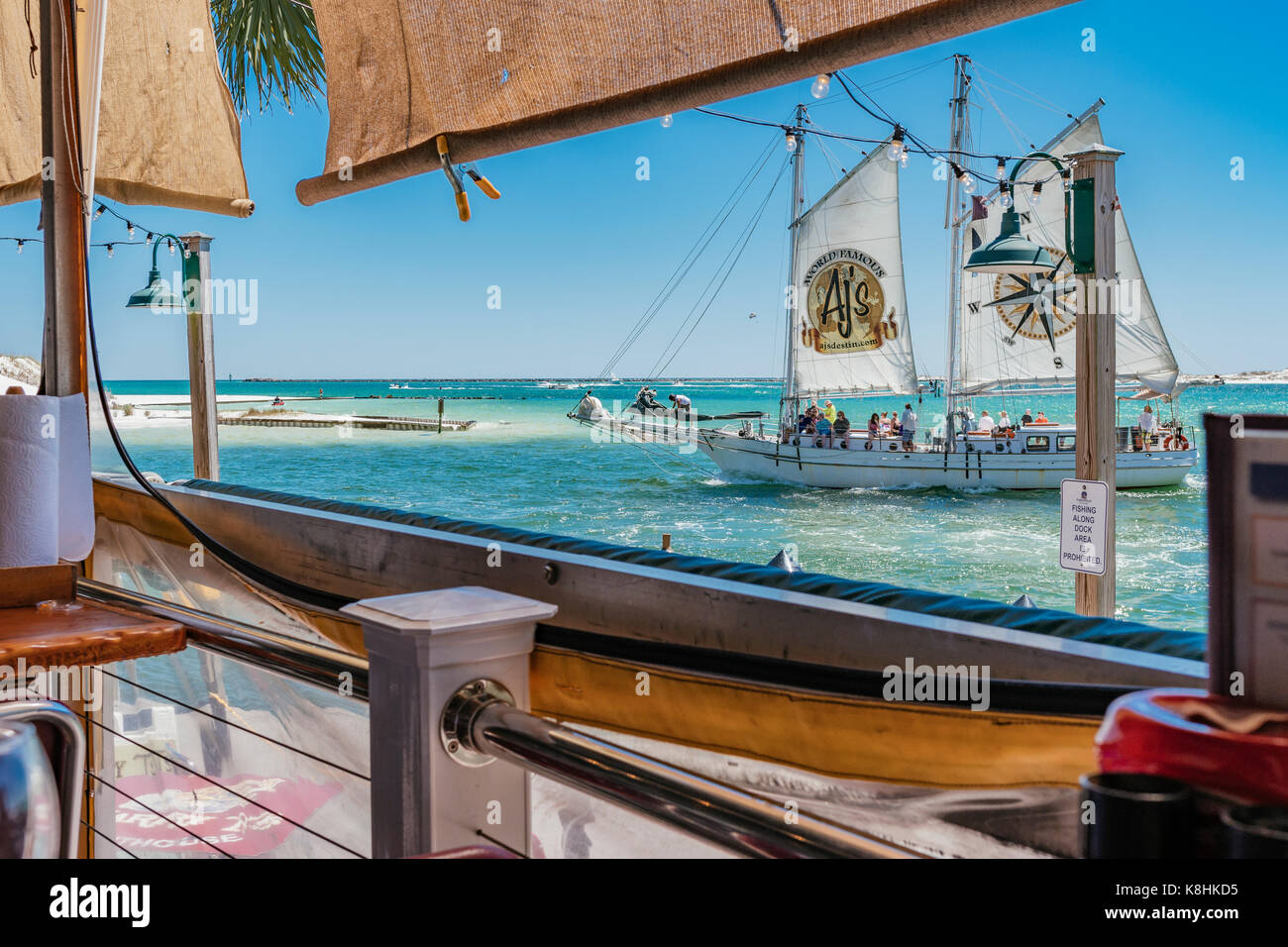View of East Pass with a passing sailboat, in Destin Florida, from Harry T's restaurant, at Harborwalk Marina.Stock Photo