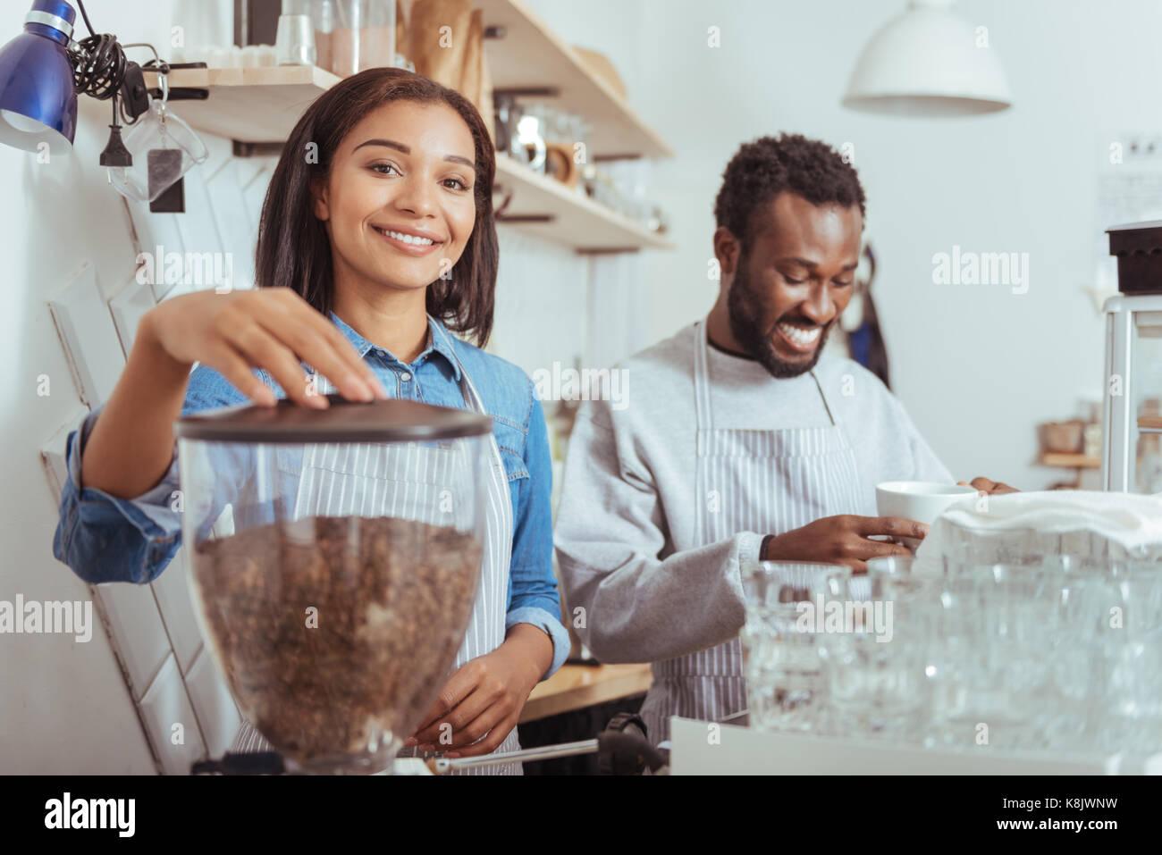 Cheerful new baristas training their coffee-making art - Stock Image
