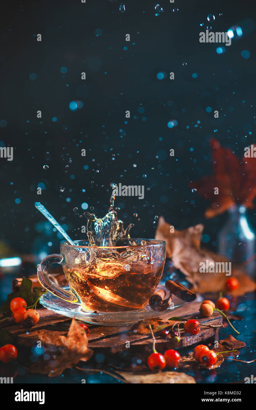 Action autumn still life with tea cup, wooden coaster, autumn leaves and berries, teaspoon and a frozen in motion - Stock Image