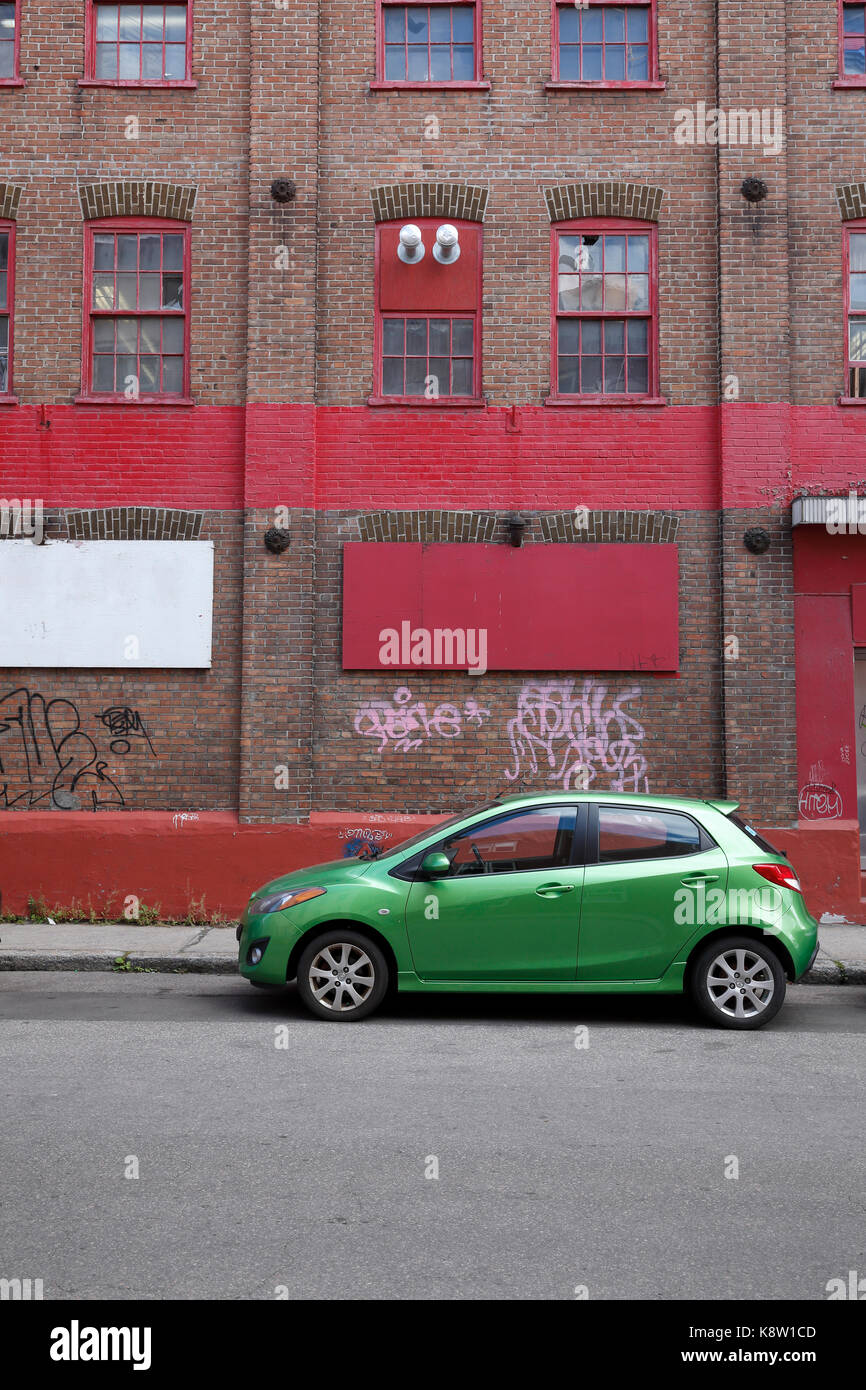 green car parked in front of red building - Stock Image