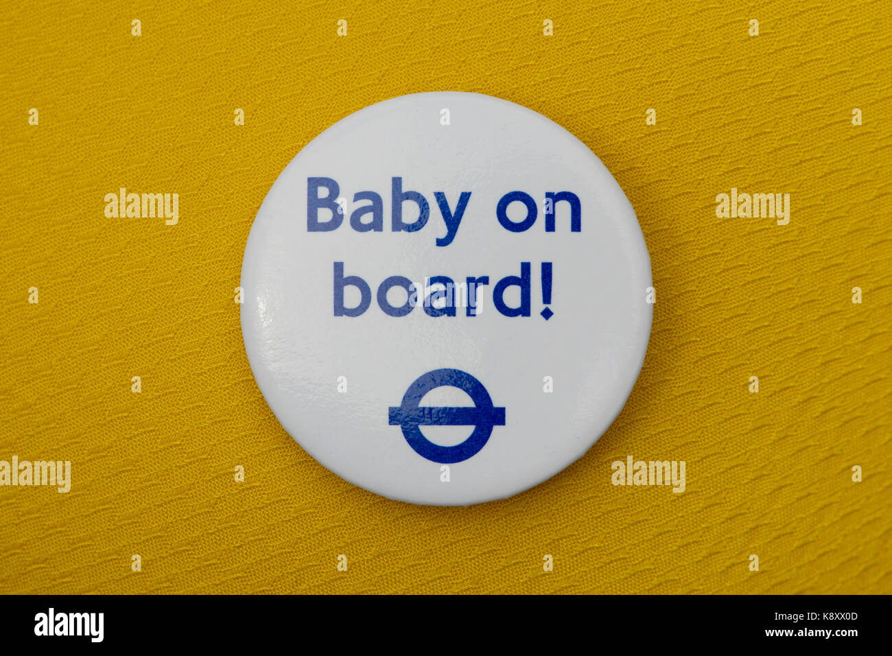 A London Underground Baby on Board badge worn on a yellow fabric garment (Editorial use only). Stock Photo