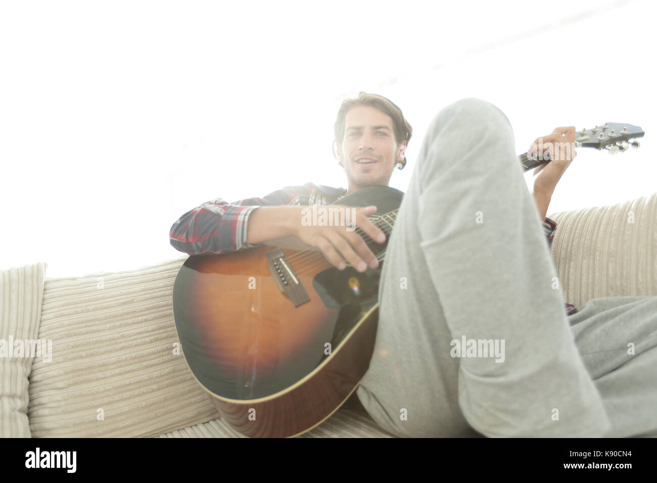 guy with guitar sitting on sofa in living room. concept of a lifestyle - Stock Image