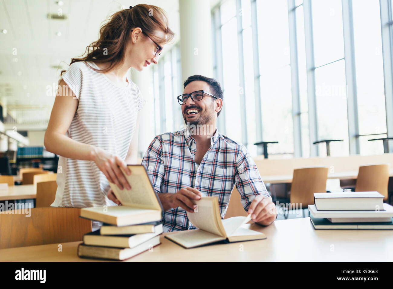Young attractive students spending time in library - Stock Image