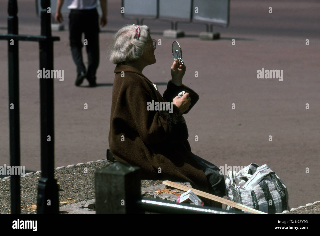 elderly woman outside seated looking at her face with a hand mirror checking her make-up - Stock Image