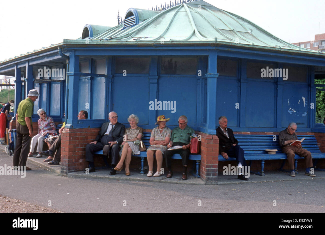 Elderly people at a seaside resort seated in a pavilion enjoying the sea air - Stock Image