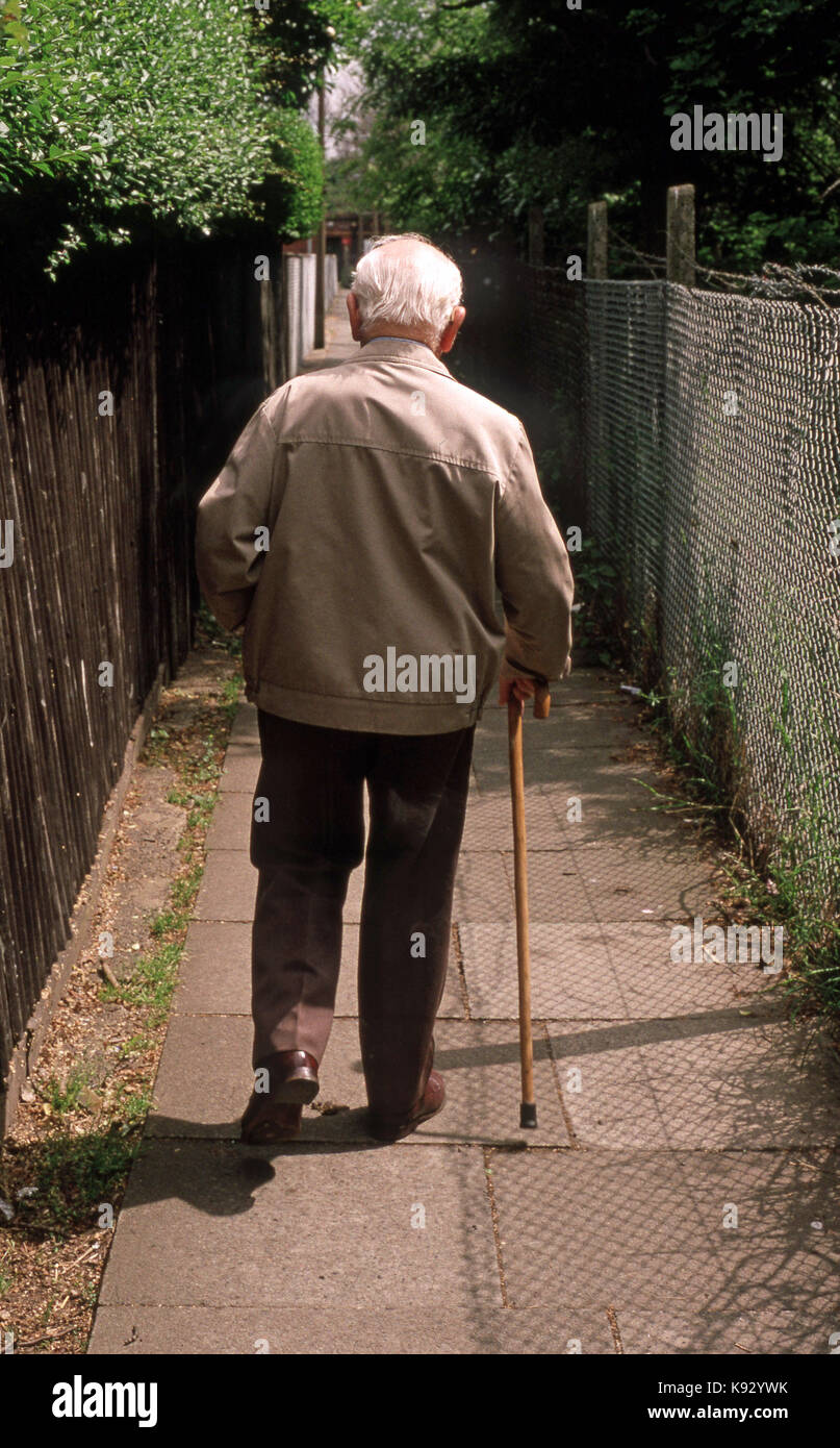 Old Man walking alone down a narrow lane aided by a walking stick - Stock Image