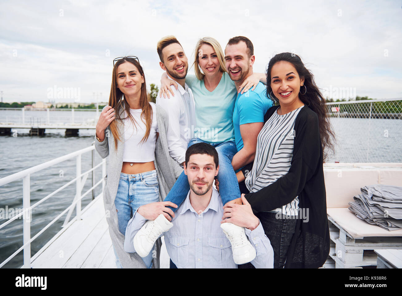 Portrait of a group of young people sitting on the edge of the pier, outdoors in nature. Friends enjoying a game - Stock Image