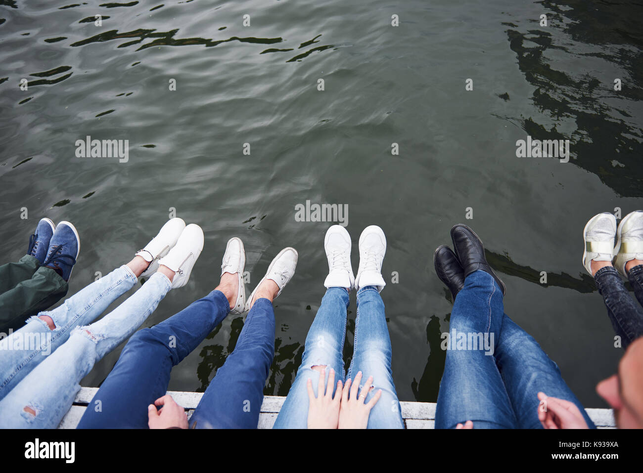 Young people friends sitting on the river bridge, lifestyle, feet over blue water - Stock Image