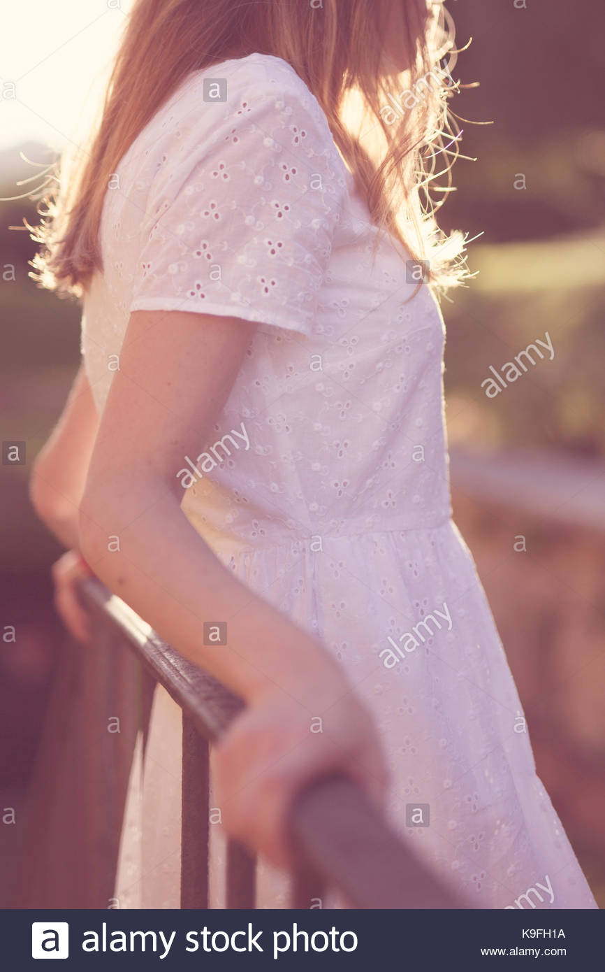 Girl leaning against a fence at sunset, back lit, summer feel - Stock Image