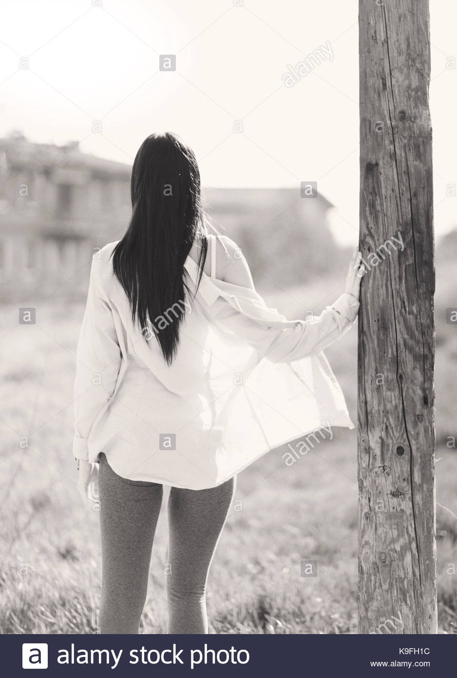 Black and white portrait of a girl leaning against a pole - Stock Image
