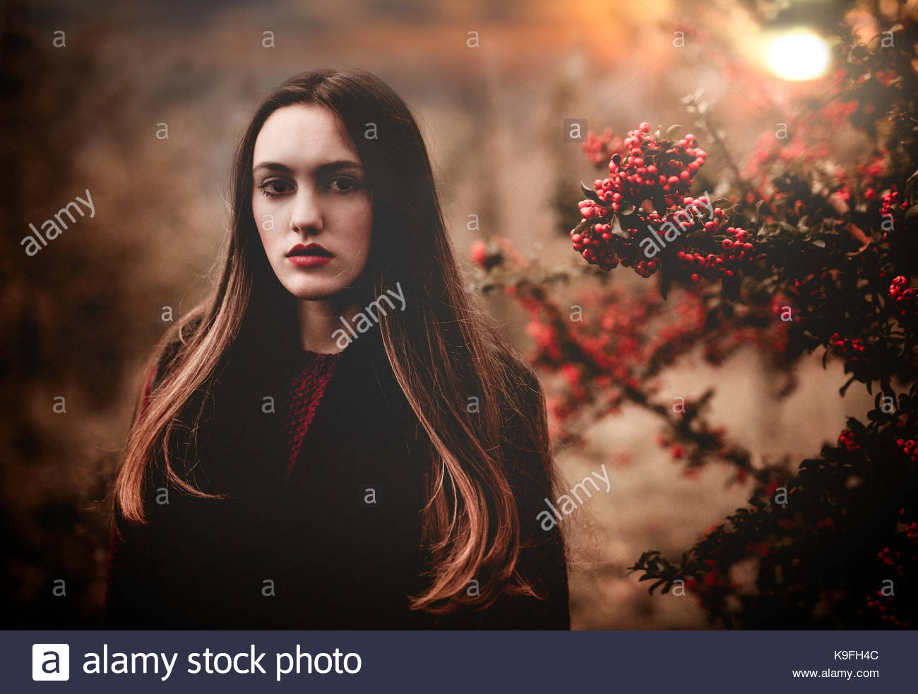 Girl standing near a berry plant, at sunset, in the woods - Stock Image