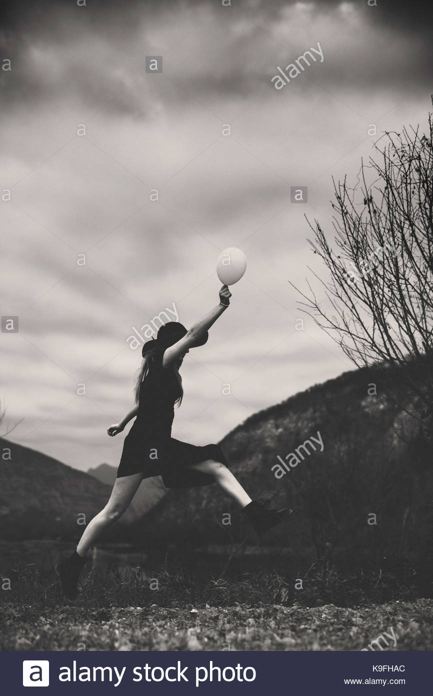 Lady in a field: jumping holding a white balloon - Stock Image