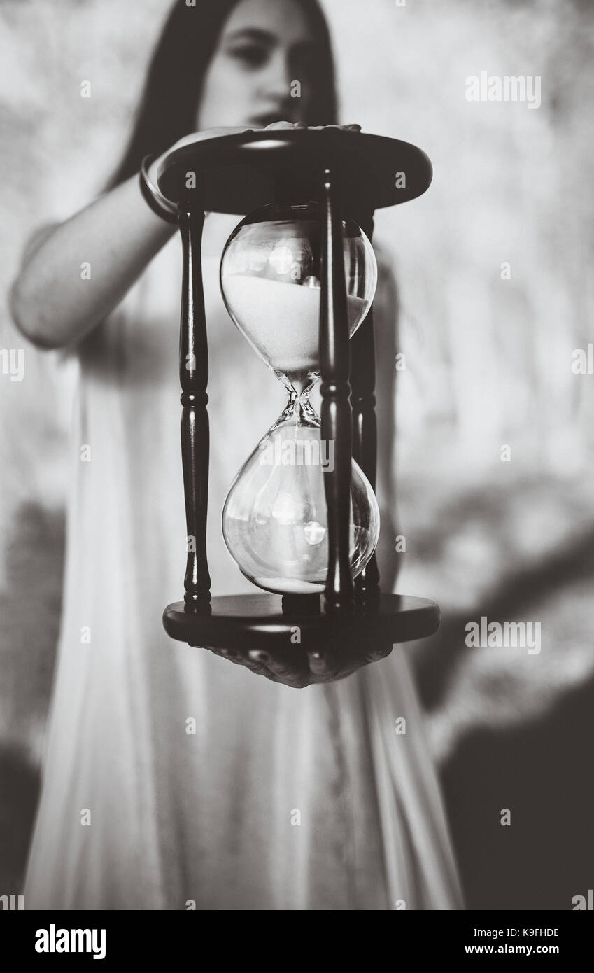 Black and white portrait of a girl holding an hourglass - Stock Image