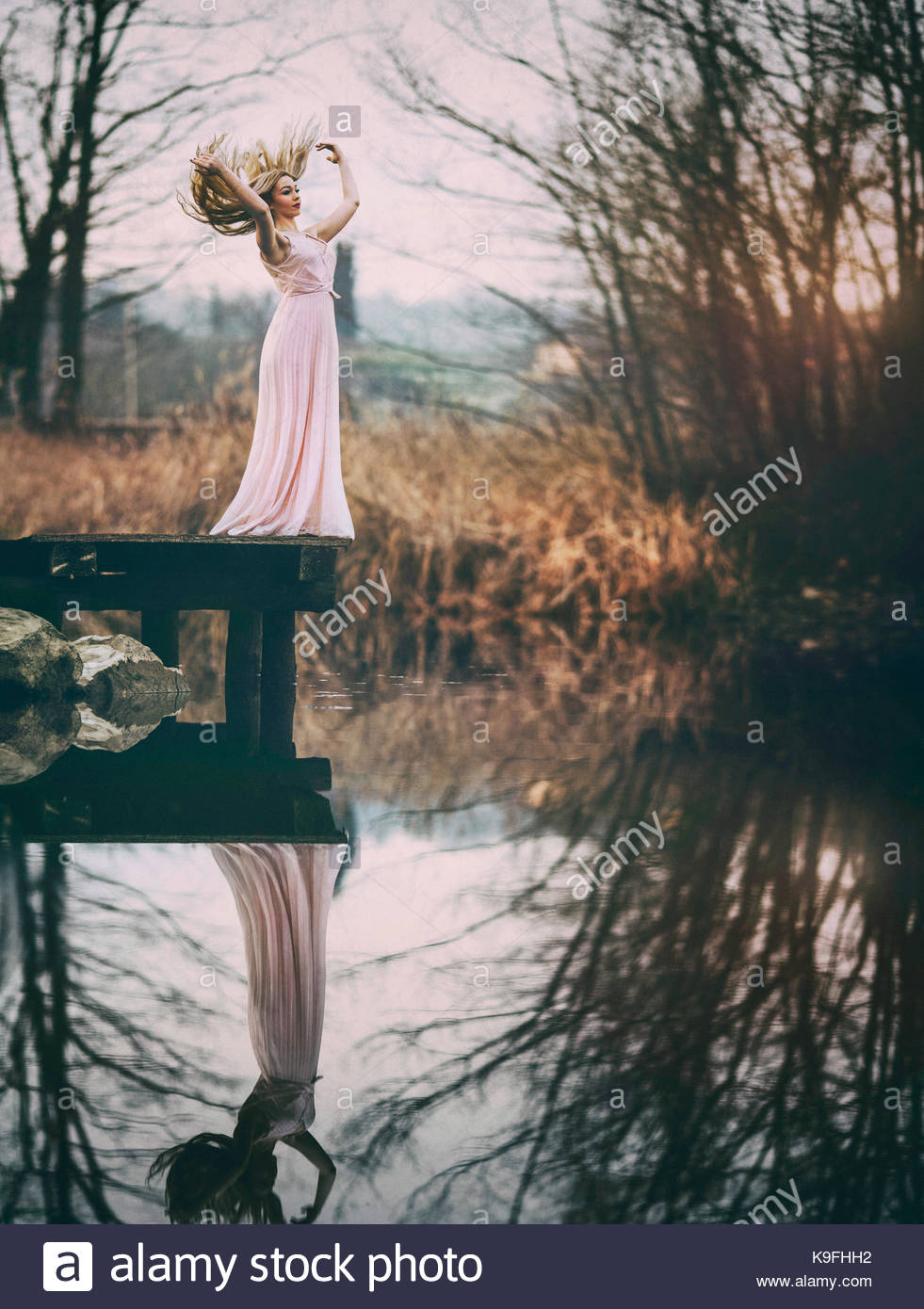 Lady in pink dress by a pond: beauty in nature - Stock Image