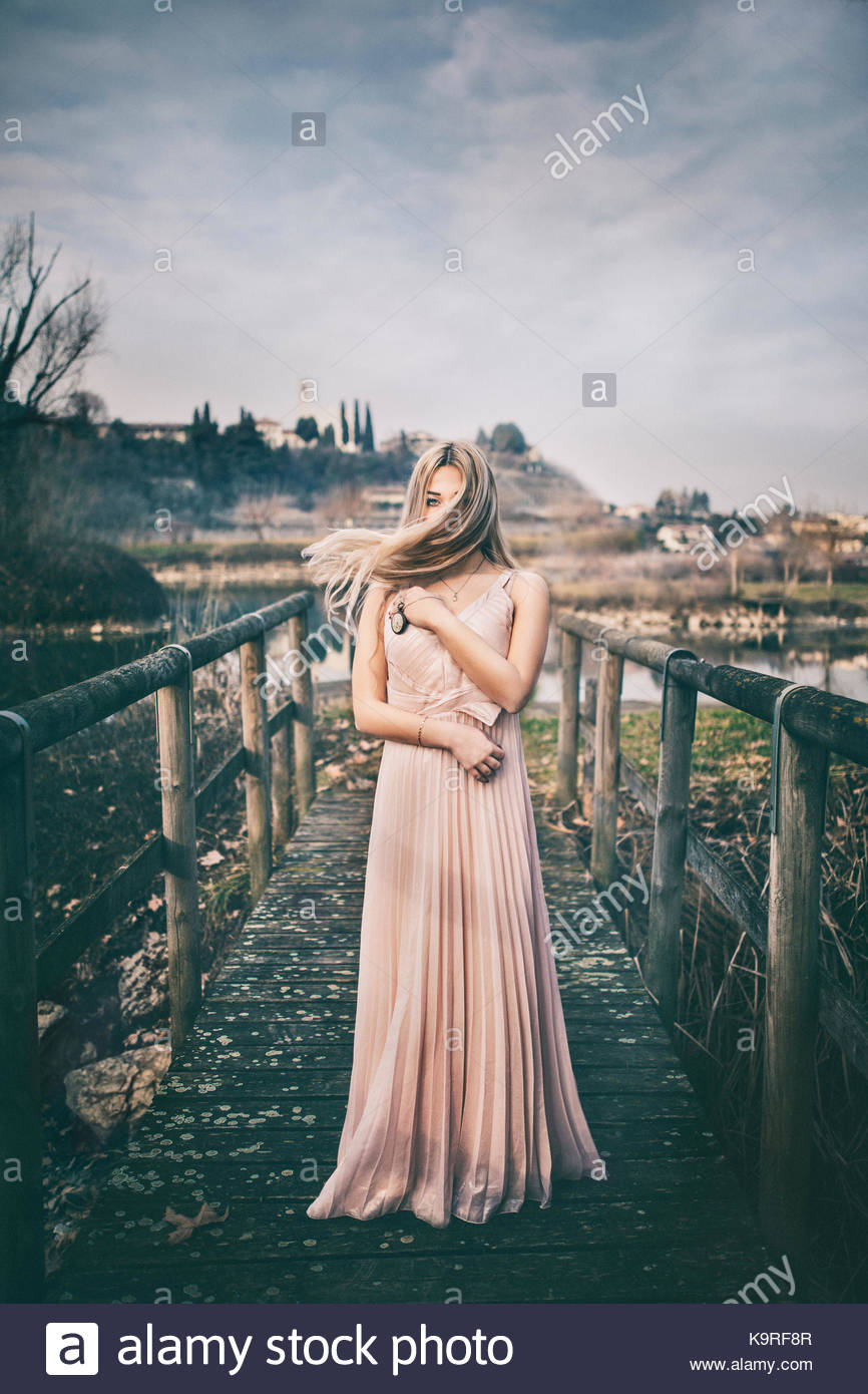 Portrait of a girl standing near a pond. Hair is moving. Blonde hair. Dreamy looks. Pastel colors. Light pink dress. - Stock Image