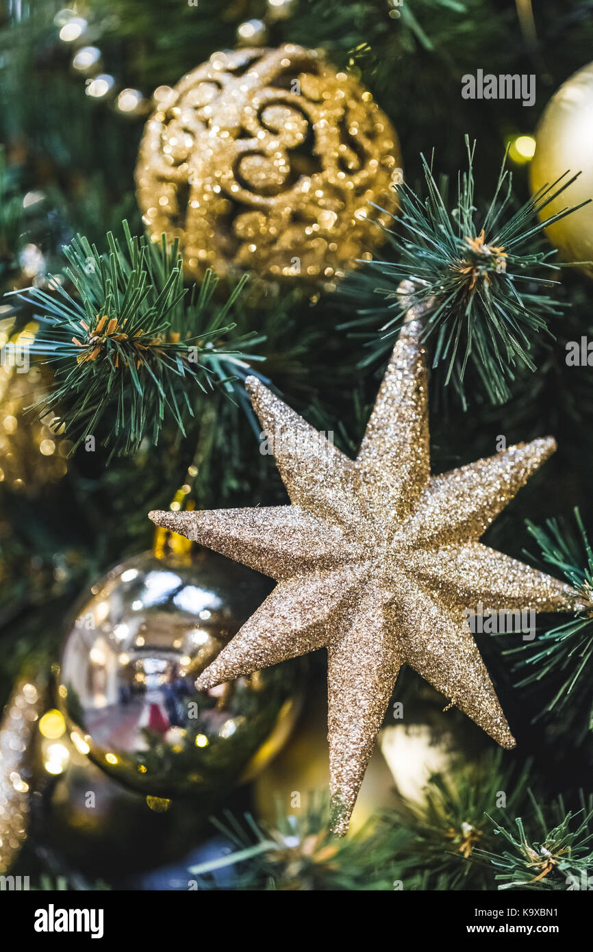 Decoration of the Christmas tree in the form of shiny gold stars, New Year mood - Stock Image